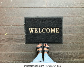 Top view of selfie feet in sandals shoes on mat with welcome message on wooden floor background