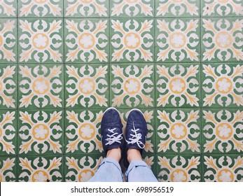 Top view selfie of feet in sneaker shoes on vintage art pattern floor with copy space