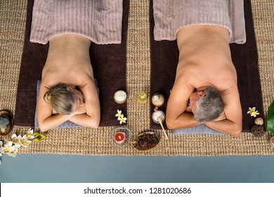 Top view of senior couple lying on front at wellness spa. Mature man and woman lying naked spa equipment's and flower around thewithm. High angle view of relaxed couple enjoying spa treatment.
