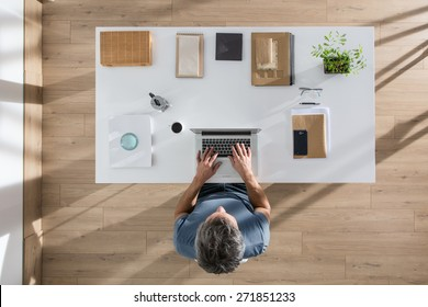 top view, senior executive sitting at  desk and working on his laptop, his table is perfectly tidy, the sun casts graphics shadows on the wood floor