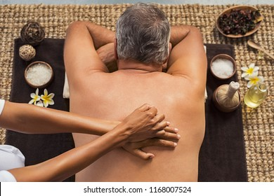 Top view of senior man lying in a spa having a back massage. High angle view of mature man lying on front at the physiotherapy gets massage. Male beauty treatment concept.