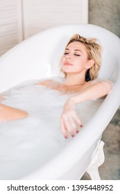 Top view of sensual sexy woman with blonde hair, pretty face with makeup, lying in bath with closed eyes, enjoying good rest, relaxing in foam water in bathroom. Pleasure, Spa and body care concept.
