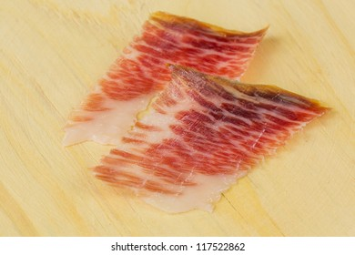 Top view of serrano ham slices over wood