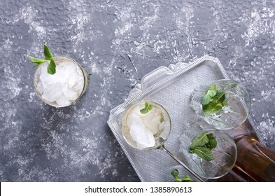 Top view of served mint julep drink on the vintage silver tray. Glasses and mint in it, crushed ice and bottles of alcohol beverage