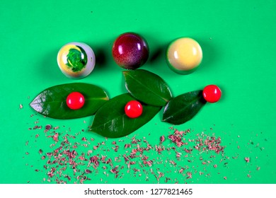 Top view of set of beautiful and delicious chocolate sweets decorated with assorted chocolate crumbs and decorated with green flowers isolated on a green background. Broken chocolate pieces