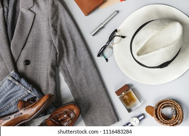 Top view set of classic clothes, plaid blazer, brown tassel loafer, brimmed straw hat and accessories on grey background