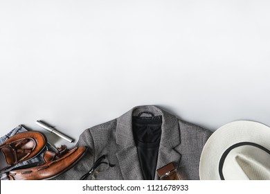 Top view set of classic clothes on grey background, plaid blazer, brown tassel loafer and accessories with copyspace