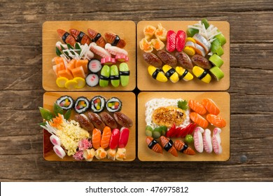 Top view of Set of Miniatures Sushi Bento on Tray on wooden background.
