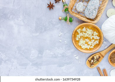 Top view of set for relaxing healing thai spa treatments. Basket with massage stones, bowl with flower water, salt, herbal pouch, essential oils are on grey cement concrete background. Ayurveda salon