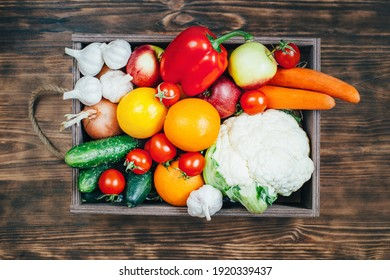 top view of a set of vegetables and fruits products in a wooden box on a wooden table