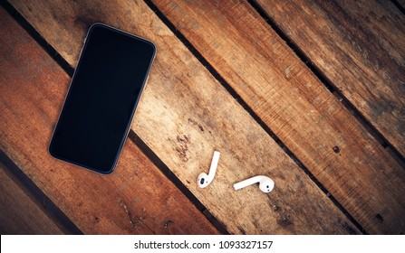 A top view of a set of wireless earbud headphones and mobile phone blank template lying on a rustic wooden table.