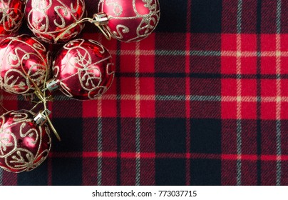 Top view of several Christmas ornaments atop a red, black and white tartan cloth with room for a message.