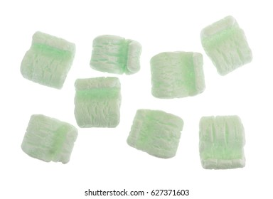 Top view of several green polystyrene packing peanuts isolated on a white background.