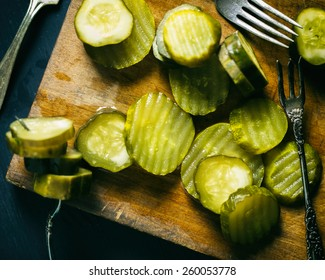 Top view of several pickle slices on a cutting board with antique forks.