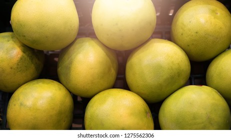 Top view of several pomelos yellow green color lying in plastic box. Pomelos in the plastic box for sale in the market. Pattern of pomelos