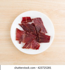 Top view of several slices of hardwood smoked beef jerky on a white plate atop a wood table top.