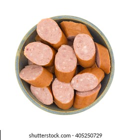 Top view of several slices of reduced calorie kielbasa sausage in an old stoneware bowl isolated on a white background.