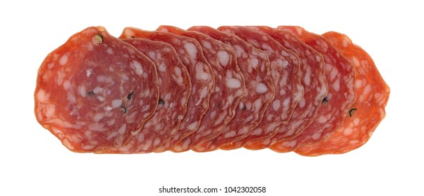 Top view of several slices of uncured soppressata dry salami in a row isolated on a white background.