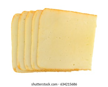 Top view of a several stacked slices of muenster cheese isolated on a white background.
