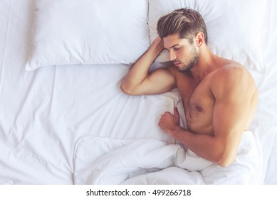 Top view of sexy muscular young man sleeping in bed