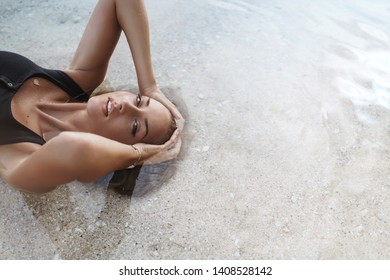 Top view sexy sensual blond woman lie sea water sandy beach touch wet hair look camera flirty sexy alluring gaze sunbathing wear black bikini enjoy paradise resort, summer holiday, vacation concept