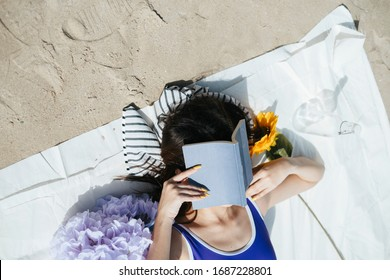 Top view - Sexy young asian woman on purple swimming suit and blue jeans laying on a mat, reading a book in the beach, sunbathing in summer season.