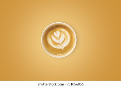 Top view of shaped designed cup of latte or cappuccino coffee on golden background.