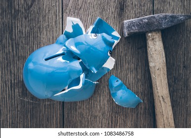 top view of shattered piggy bank and hammer on old rustic wooden table