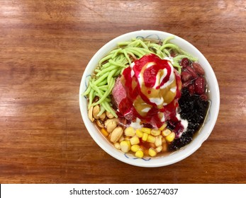 Top view of shaved iced with ice cream dessert called Ice Kacang or ais kacang in Malaysia with mix ingredients of peanuts, red beans, milk, red syrup and colorful sweet jelly.