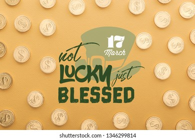 top view of shiny golden coins near not lucky just blessed lettering on orange background