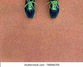 Top view of shoes used for men's running on a red rubber surface of running track.background with copy space.concept for healthy and active lifestyles.