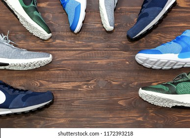 Top view shop display of unbranded modern new stylish sneakers running shoes for men on wooden background texture with copy space.