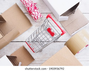 Top view of shopping cart with box, tape and string on wooden table for entrepreneur preparing for shipping, packing, selling online, e-commerce concept. Startup business