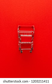 top view of shopping trolley on red background. minimalist photo of pushcart with some copy space around
