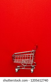 top view of shopping trolley on red background. minimalistic photo of pushcart with some copy space around