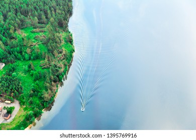 Top view of the shore of the lake. Motorboat goes on water