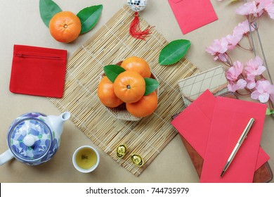 Top view shot of arrangement decoration Chinese new year & lunar festival concept background.Orange & tea pot also red pocket money with map to travel.Variety object on modern brown wood at home desk.