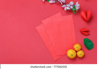 Top view shot of arrangement decoration Chinese new year & lunar festival background concept.Orange & red packet money also DIY paper crafts fortune cookies.object on modern red wooden at home desk.