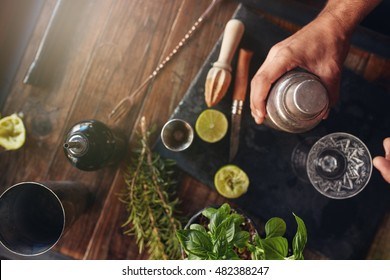 Top view shot of barman hand holding cocktail shaker on table with ingredients.