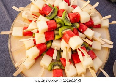 Top view shot of a  big wooden plate full of fruit skewers made with watermelon, pineapple and kiwi. Healthy catering vegan and gluten free desserts.