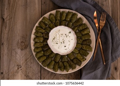 Top view shot of delicious stuffed grape leaves dolma on round plate served with yogurt and dried mint. Horizontal composition. Copy space.