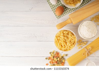 Top view shot of dry pasta with spaghetti and ingredients for pasta on white wood background.
