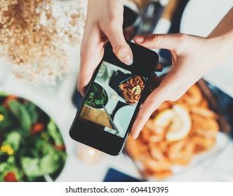 顶视图拍摄的女性手拍摄的食物,年轻的时髦女孩制作美味的地中海食物表的照片