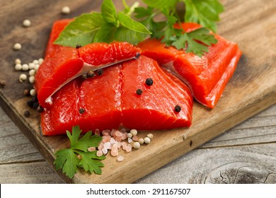 Top view shot of fresh bright red Copper River salmon fillets on cutting board, sea salt and herbs.