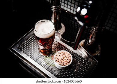 A top view shot of a glass of lager beer with a cup of peanuts on a metal screen tray - Shutterstock ID 1824035660