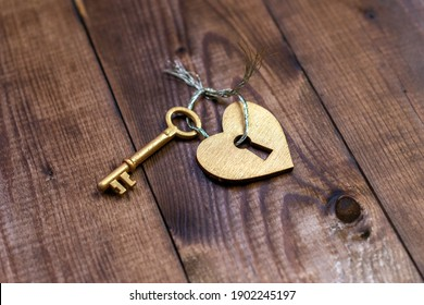 Top view shot of gold heart and key on wood background with copy space