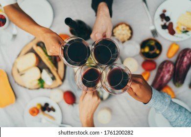 Top view shot of group of people toasting with wine glasses, Summer holiday party, Celebration Vacation People, Best friends celebrating at birthday party, Closeup of hands cheering with red wine