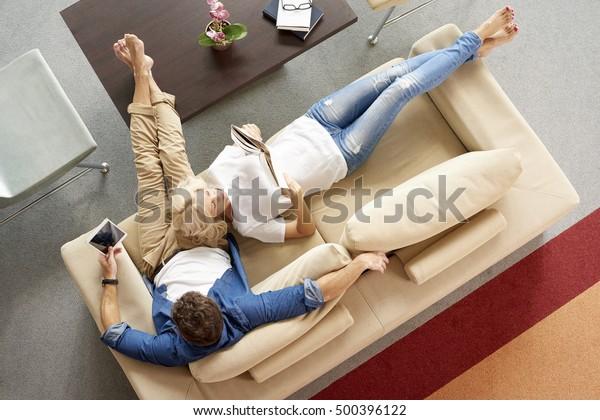 Imagen de primera vista de una pareja de mediana edad relajándose juntos. Hombre con una tableta digital sentado en el sofá mientras mujeres rubias yacen a su lado y leen un libro.