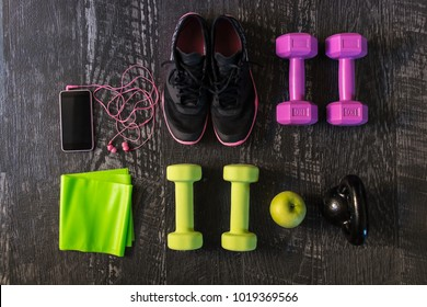 Top view shot of a pair of women sport shoes, multiple dumbbells,  kettle-bell, fitness gum, smart phone with headphones and an apple aligned on a dark wooden floor background. Training concept