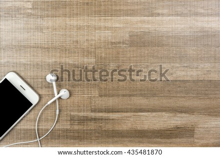 Top view shot of phone and earphones on wooden background. Flat lay shot with copy space